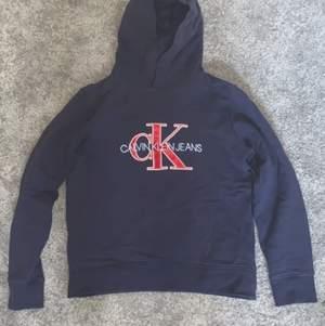 En fin marinblå Calvin Klein hoodie med in broderat Calvin Klein jeans i ljusblått och tryckt CK i rött Trycket är lite slitet efter tvätt men ändå i bra skick (8/10)