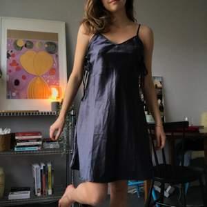 Mörkblå kort lite utsvängd klänning i siden, med knytning på sidorna. Tyvärr för stor för mig.