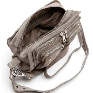 Supersnygg väska i äkta läder från NUNOO.     Väskan har: - Ett stort fack som försluts med dragkedja - Två innerfack - Tre ytterfack med dragkedja - Axelbandsrem med nitar - Längre axelbandsrem för crossover (avtagbart) Längd 25 cm, bredd 10 cm, höjd 16 cm.                     Ordinarie pris 1499:-.