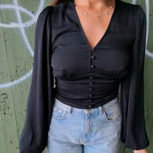 Säljer denna jättefina svarta toppen i storlek small🖤 Toppen är i silkesmaterial med puffiga armar och korsetliknande-design i midjan. Använd ett fåtal gånger så är i princip i ny skick✨✨
