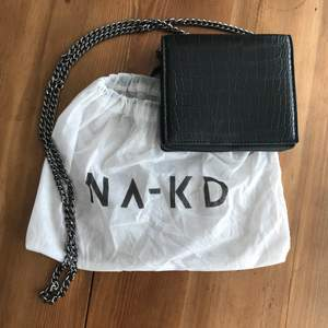 """Nypris 249 kr. """"Croco Mini Messenger Bag"""" Den här väskan från NA-KD Accessories har ett huvudfack med en tryckknappsstängning, en innerficka med en dragkedjestängning, en justerbar kejdehandtag och en ormimitation. This bag comes in black. Height: ca. 12 cm / 4.7 in. Width: ca. 3 cm / 1.2 in. Length: ca. 14 cm / 5.5 in. Material: Outer Shell: 100% Polyurethane. Lining: 100% Polyester. Brand new item, JUST without tags. Comes with dust bag. Never used and only tried on for two minutes. Only handled when I took the pic, the rest of the time was in my closet. Happy to bundle. Will gladly take more pics. Smoke and pet free storage space. No other flaws to note.    **TRACKED SHIPPING VIA POSTNORD**"""