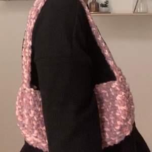 En handgjord virkad shoulderbag men rosa och lila mönster. Den är aldrig använd och väldigt unik. Jag står för frakten så om ni är intresserade är det bara att skriva till mig. Självaste väskan är 27x13 cm lång.