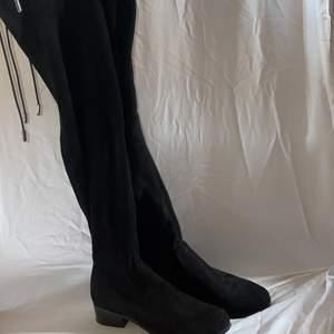 Svarta skinnimitations overknee-boots från Nilson Shoes med en 3,5 cm klack - i väldigt bra skick (använd ett fåtal gånger). Högst upp på skon finns snören som kan knytas som en fin detalj (se sista bilden). Tyvärr ger bilderna inte en rättvis bild av hur skorna ser ut eftersom de är svåra att fota - skriv privat om du vill ha bilder på hur skorna sitter på.  Storlek: 37 (true to size). Nypris: 799kr. Mitt pris: 190kr + 110kr frakt. Budgivning i kommentarerna eller köp direk