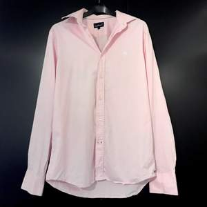 Ljusrosa skjorta i tunt material från EastWeast i storlek M. 100 % Bomull. Fint skick! Till er som inte ännu upptäckt hur fantastiskt det är med en bomullsskjorta på sommaren (och alla andra årstider) kan jag bara säga: Prova!