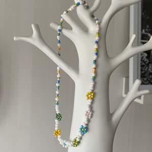 Ett handgjort färgglatt halsband med blommor gjort av seedbeads 🧡💛💜
