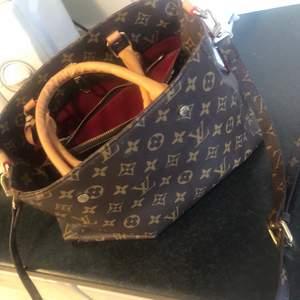 En Louis Vuitton väska som är en kopia i bra skick jätte fräsch och har brett utrymme för att ha saker där i.