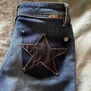 Ett par mörkblåa lågmidjade jeans med stjärna på rumpan som jag sytt på själv