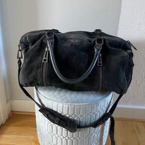 Jag säljer en sliten väska från Zadig & Voltaire i modellen Sunny. Väskan är i svart mocka och nypris var mellan 4000-5000kr men den är sliten så säljer den därav väldigt billigt. På ena kortsidan där man fäster remmen är fästet sönder (se bild 3) men det går säkerligen att fixa om man tar den till en skomakare eller läderverkstad eller liknande. Utöver detta är väskan i ett allmänt använt skick. Det är en otroligt fin modell, den rymmer väldigt mycket. Mått är ca bredd 34cm höjd 23cm djup 17cm.
