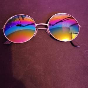 Runda solglasögon med regnbågsglas. väldigt lite slitna på ena glaset men inget som stör. PM för mer bilder/info
