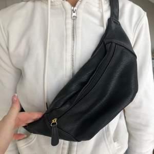 väska i svart med guldiga detaljer, köpt från pieces