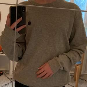 En grå sweatshirt ifrån märket NN07! Tröjan är i storlek M men passar mig som är 165 cm (bär vanligtvis S). Kan skicka fler bilder! Tröjan är en killmodell men sitter fortfarande bra