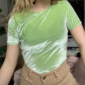 En grön sammets T-shirt i supercoolt material, mjuk och stretchig! Väldigt fint skick och passar storlek XS-L även fast det står storlek L.