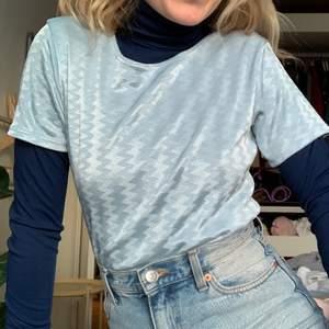 En blå tshirt som har ett glansigt, mönstrat material. Den är stretchig och knappt använd. Så fin på sommaren! Passar XS-L.