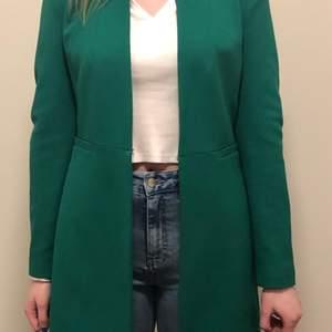 Jättefin vår kappa från Zara i strl S. Grön, dock inte riktigt som den blev på fotot. Klarare grön i verkligheten så inte med den blåtonen i det gröna. Knäpps fram med en lite dold hake. Knappt använd
