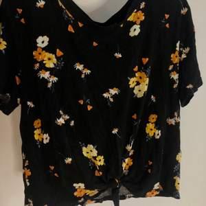 Svart T-shirt med blommor. Fladdrigt material. Perfekt till varma dagar. Strl S men då det är så fladdrigt passar det till XS och M.