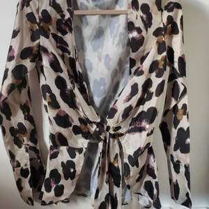 En fin satin blus/topp från boohoo med leopardmönster och knytdetalj. Aldrig använd endast provad.