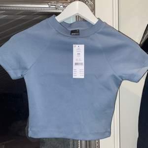 Croppad tröja i blå/grå från Ginatricot nypris 229kr! Aldrig använd. Har även storlek M som jag aldrig använt. Det är tränings material. Sista bilden ger mer rättvisa på färgen.✨