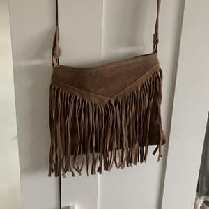 Brun axelbandsväska med justerbart band. Väskan är köpt i en butik i Spanien och är aldrig använd. Den är rymlig till vardagliga saker:) köparen står för frakt.