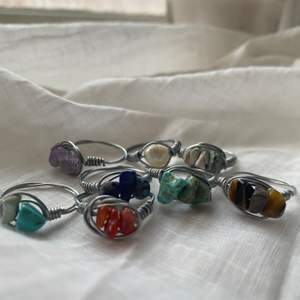 """Säljer kristall-och stenringar som jag själv har gjort! :) Jag gör ringarna i """"standard"""" storlek, men om du har större/mindre fingrar så är det bara att skriva det, så fixar jag :).  Ringarna går att få med små stenar/kristaller i form av """"chips"""". Jag har följande; -Halvädelsten (grön) -Karneol (orangebrun) -Ametist (lila) -Jade chip (turkos) -Lapis lazuli (mörkblå)   -Bergkristall (genomskinlig) -Tigeröga (brun) -Sötvattenspärla. Alla ringar kostar 20kr/st. Kom gärna med förslag på olika kombinationer eller idéer om du skulle vilja ha det :)."""