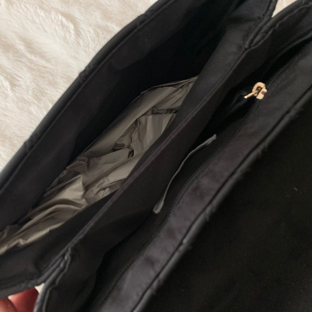 Säljer en helt oanvänd svart och guld mindre väska, alla detaljer på den är i guld. Papper är kvar inuti från när den köptes. Säljer för 120 kr. Köparen står för frakten! . Accessoarer.