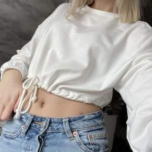 En vit croppad tröja från shein med knytning där nere. Aldrig använd, säljer då den aldrig kommit till användning. Köparen står för frakten