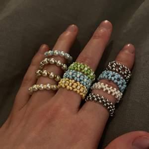 """Ringar av pärlor. Finns fyra olika designs just nu. De görs i """"vanlig"""" storlek så ringen lär passa något finger.   Alla ringar går att få i grön, blå, vit, gul, guld (med bruna toner) och silver.  Alla ringar kostar 30kr/st förutom de blommiga ringarna. De kostar 45kr/st Frakt 12kr per beställning🌸❤️"""