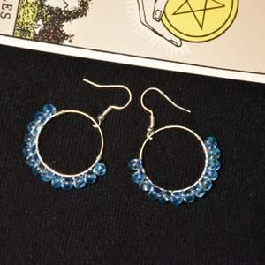 Örhängen med ljusblå skimrande glaspärlor och nickelfria krokar.