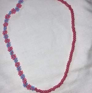Modernt och populärt pärlat halsband, halva sidan med rosa och blåa blommor och andra sidan med rosa seed beads. Se gärna mina andra annonser för fler halsband och ringar.