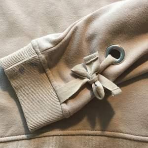 Beige sweatshirt storlek S. Jättefin knytdetalj på båda armarna. Lite nopprig och lite blå färg på ena armen, därav priset. Möts Stockholm/fraktar🥰