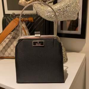 En Gucci väska, vet ej om den är äkta för det e min mammas gamla väska så det finns bara en av den så limitedition, finns ett band så man kan hänga den runt halsen eller bara ha den så som den är, även det är skit snyggt och coolt, den är i ny skick buda i kommentarerna om det är många intresserade, höj med minst 15kr ❤️