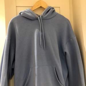 Hoodie från Monki i en jättefin ljusblå färg! Användt endast en gång innan. Storlek M men passar från S-L beroende på hur oversized man vill ha den! Köparen står för frakt.