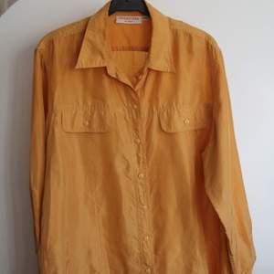 Lindex 42/44. Oversized brandgul skjorta i 100 silke. Superfin färg!! Finns en liten reva bak på ryggen som jag kan skicka bild på om man är intresserad. Säljer billigt🥰
