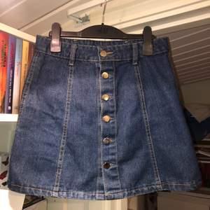 En mörkblå jeanskjol med silvriga knappar. Står storlek M i men skulle säga att den är mer åt S/XS hållet. Blir din för 20kr + frakt 🧵