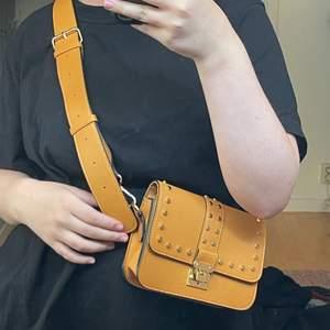 Säljer denna gul/orange väska med nitar som är oanvänd. Bandet är avtagbart! 💕💕