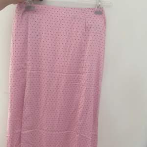 Jättefin rosa prickig kjol i siden material från H&M. Kjolen har även två slitsar. Aldrig använd, prislapp kvar. Finns två mini hål som syns på sista bilden som jag märkte efter jag köpt kjolen. Syns inte alls dock. Skriv för fler bilder om det behövs🥰