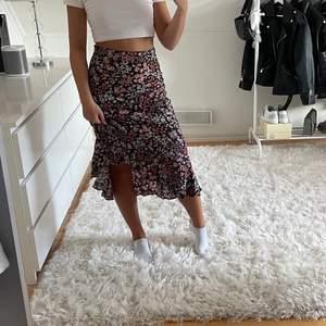 Blommig kjol som är halv lång med volanger. Storlek 34. Köparen står för frakten. Pris kan diskuteras