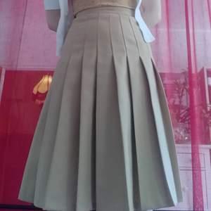 🐫 Otroligt fin kamelfärgad plisserad kjol från Lundberg & Wester! Gissningsvis 70-tal. Märkt storlek 36 men se mått. Köpt från Kungliga Operans kostymlager, därför märkt med (antagligen) karaktärens namn. Materialet är en polyester- och ullblandning, kjolen är även fodrad. Stängs med dragkedja (ser nybytt ut) samt matchande knapp. Fint skick!  Mått mätta med kjolen på: Midja: 66cm Stuss: 91cm Längd: 67cm  Pris 200 + frakt (66kr) eller avhämtning i Stockholm.