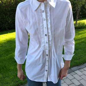 Vit skjorta med mönster vid knapparna. 77 cm lång/ 44-45 cm bred. Storlek EU 42 vilken jag antar är en L/XL. Jag är 182 cm lång och väger 73 kg.