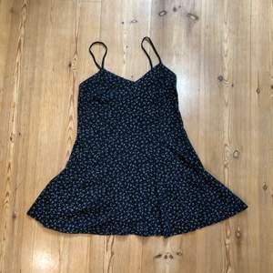 Svart klänning med ljusblå blommigt mönster. Klänningen är i storlek 38/40 men är rätt kort och liten vid brösten. Lite trådar som lossnat. 🌷  86 kr (postnords spårabara frakt på 66 kr, är inkluderat i priset 📦 )