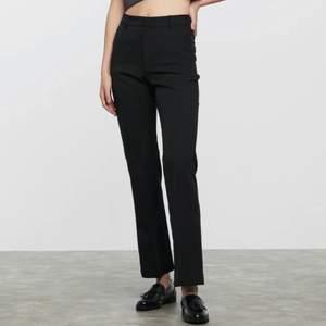 Ett par as snygga svarta kostymbyxor. Mid/high waist suit pants i ett halvt stretchmaterial. Flared legs med veck, sidofickor och falska fickor på baksidan.  Dragkedja, knapp och metallögla som stängs framför.