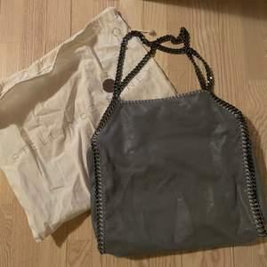 Stella McCartney Bag Grå Falabella kedjetrimmad tote väska från STELLA MCCARTNEY med kedjelänk, magnetfäste, logotyp charm, invändig ficka med dragkedja och foder med logotryck. Väskan är nästan som ny skick har knappt använt den.