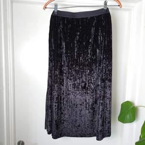 Svart kjol i krossat sammet med resår i midjan, ingen storleksmärkning men bör vara L🍒