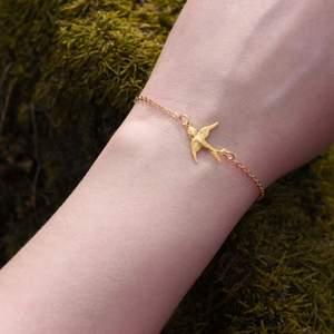 Handgjort armband med guldfärgad svala i rostfritt stål 🌼 Detta armband är cirka 17 centimeter långt inklusive låset, men längden kan justeras om du vill! Svalan är i lätt material och konvex, alltså inte solid i sin form. Kan skicka bild om du vill se! ✨ Armbandet levereras i en fin liten presentpåse. Frakt på 12kr tillkommer 💫
