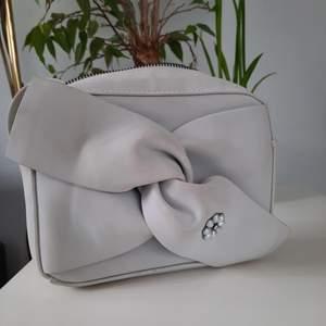 Axelbandsväska med blomma på. Grå men använd så har lite fläckar därav priset