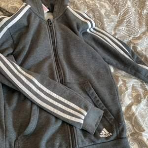 Grå adidas hoodie med dragkedja. Fint skick, inga fel. Sitter skit fint men är tyvärr lite för kort i armarna på mig därför säljer jag den.💕