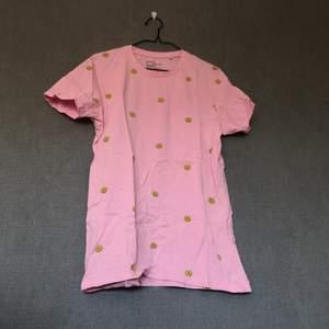 • Färgglad & härlig tisha! Go rosa nyans med klargula smileys all over. Passar till det mesta, fin färgklick i vardagen! • Storlek: M, herr • 100% bomull • Använd ett fåtal gånger, fint skick! Lite luddig i tyget efter tvätt. • +Frakt: 51kr spårbart