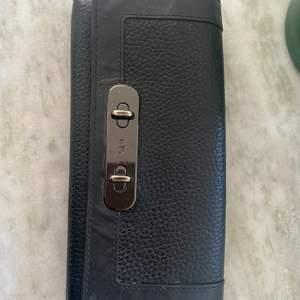 Jättesnygg svart plånbok från märker Coach. Det är en stor modell med många praktiska fack. Som ni ser är den använd men fortfarande i ett fint skick. Köpte den för runt 1600kr, kontakta för att lägga ett bud😇