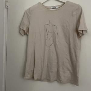 T-shirt från nakd i färgen beige med en kvinnokropp i marinblått superfin men kommer inte till användning
