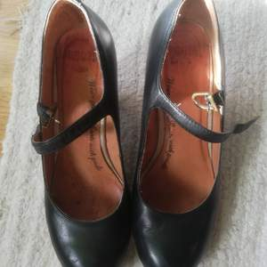 Svarta, snygga obetydligt använda skinnpums med rem över foten.