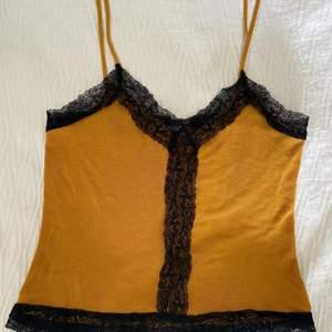 Ett senapsgult linne i superfint material med svart spets från Zara. Sitter så snyggt och passar för S-M. Endast använd en gång. Originalpris: 250 kr.